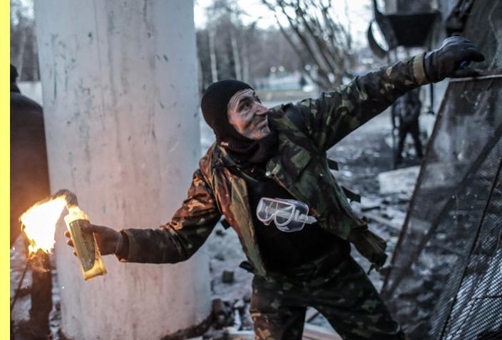 Protestatário a lançar um coquetel molotov junto ao Estádio Dynamo, de Kiev.